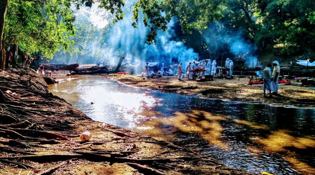 Pilgrims preparing puja in the Manik River at the Maha Kebiliththa Devalaya