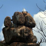 The buddha statue at the peak of the Anandakulama rocky hill of Tissa Forest Hermitage